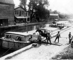 Title: Erie Canal scene, Fultonville [photograph]. Photographer/Artist: Gayer, Albert. Date: ca. 1900. Physical Details: 1 photograph : b&w ; 7 x 9 in. Collection: Perinton Municipal Historian collection Summary: Several men stand near a mule about to board a packet boat on the Erie Canal in Fultonville, New York. Mules would wear tow ropes attached to the boats traveling on the canal. As the mules walked down the towpath next to the canal, they would pull the boats along. Image Number: tpm00182 http://www.rochester.lib.ny.us/rochimag/perinton/ tpm/tpm00/tpm00182.jpg